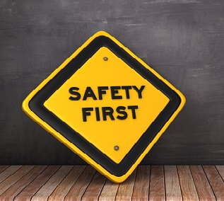SAFETY FIRST Road Sign on Chalkboard Background - 3D Rendering